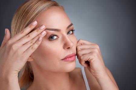 Middelbare vrouwen proberen te zien hoe te kijken dat er geen rimpels zijn