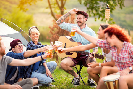 YJoyous youngsters tapping with glasses of beer in camp on open air