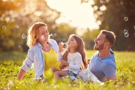 Famille avec enfants souffler des bulles de savon en plein air Banque d'images - 73427111
