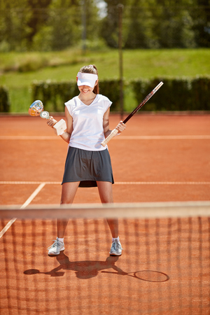 Young female winner at tennis court Stock Photo