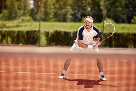 Tennis player with racket on tennis court