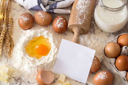 Baking background with flour, rolling pin, eggs, paper sheet