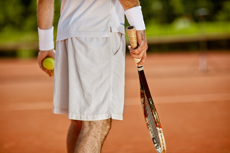Tennis player on court with racket and ball - body part, back view