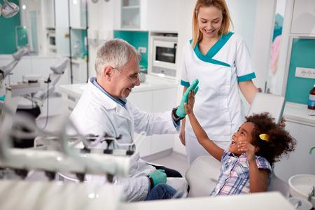 Tandarts met zijn vrouwelijke patiënt geeft vijf in tandheelkundige ambulance