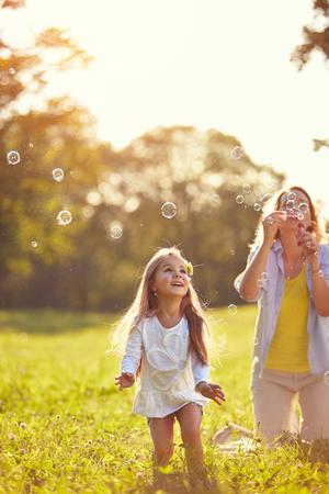 여자 아이가 밖에서 비누 거품을 쫓아 스톡 콘텐츠 - 73427204