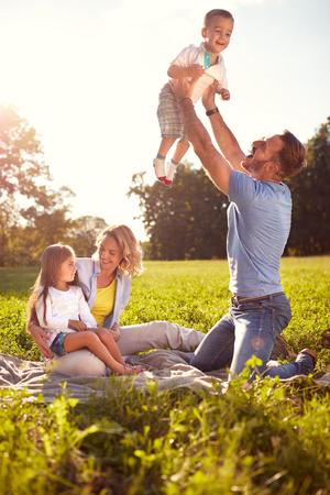 陽気な親は、子供たちのピクニックに楽しい時を過す