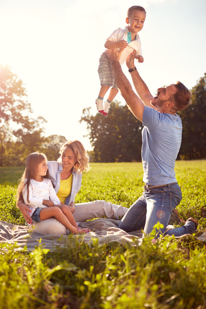 Cheerful parents have fun with children on picnic