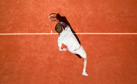 red clay: Top view of male tennis player hitting ball with racket