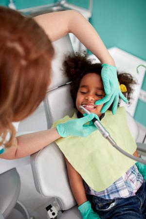 Tandpasta tanden aan jonge patiënt in tandheelkundige kliniek Stockfoto