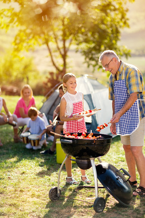 smiling grandfather and granddaughter grilling barbecue for family Stockfoto