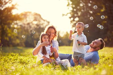 Family with children blow soap bubbles nature