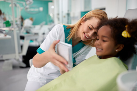 Young female dental assistant looking in mirror girls teeth