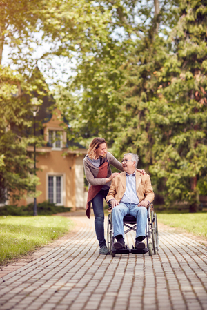 senior man in a wheelchair enjoying fresh air in a sunny day with his smiling daughter