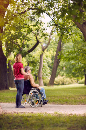 enjoying together senior man in wheelchair and daughter in the park