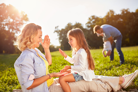 Happy woman with daughter playing on picnic outdoor