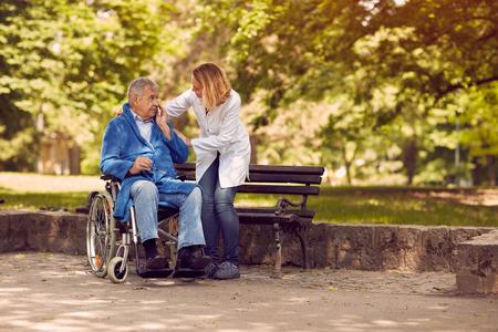Verpleegkundige helpen bejaarde hogere mens op rolstoel