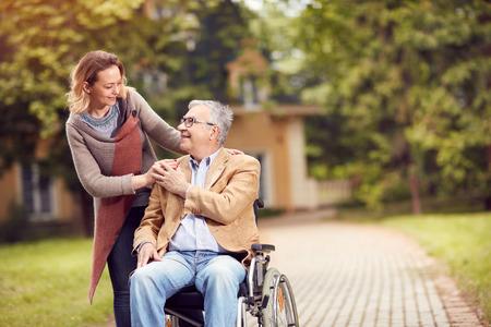 幸せな介護者の娘と一緒に車椅子で年配の男性
