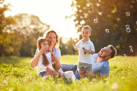 子供は石鹸泡を吹くする屋外で家族