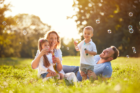 Family with children blow soap bubbles outdoor
