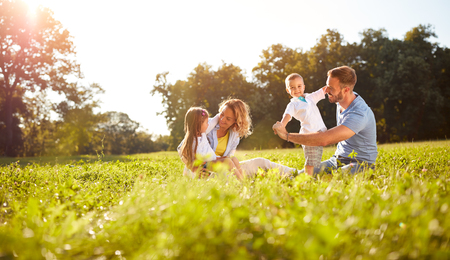 幸せな男性と女性の子供の外で遊んで 写真素材