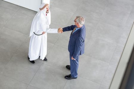 negocios internacionales: Jefe de la empresa se dan la mano con su socio de Arabia Foto de archivo