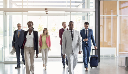 International multiethnic businessmen group arrive at airport foyer photo