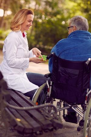 Enfermera de hospicio que da medicina al hombre mayor en silla de ruedas al aire libre