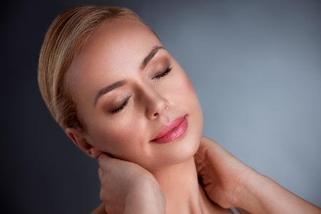 미소하고 그녀의 목을 만지고 완벽한 피부와 관능적 인 중년 여성
