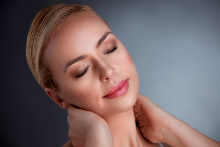 Sensual middle age woman with perfect skin, smiling and touching her neck Stock Photo
