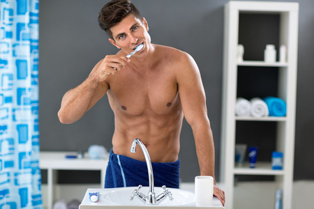 muscled: man brushing the teeth in the bathroom front of sink