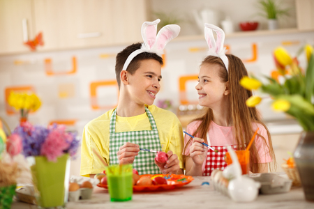 Brother and sister on creative work with paints for Easter eggs Stock Photo