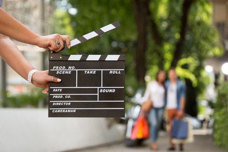 filmmaker: Female  holding clapper board with shopping couple in background, concept start sale Stock Photo