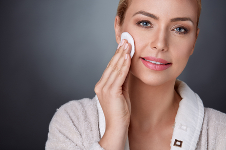 skin care woman: nourished middle aged woman cleaning her perfect skin  with cotton pad