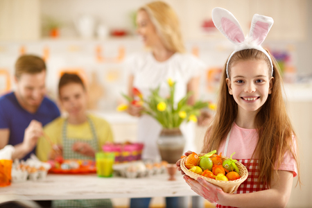 Girl hold basket full of colorful Easter eggs Stock Photo