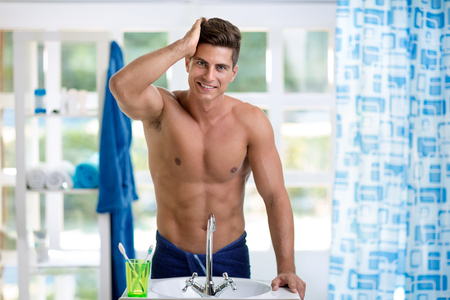Young smiling man looking at hair in mirror Stock Photo