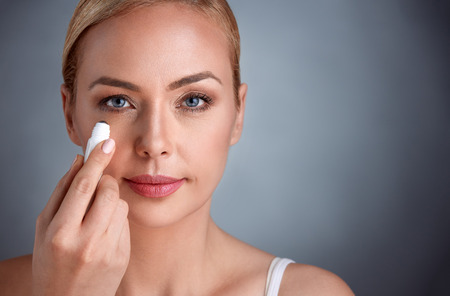 beautiful woman putting concealer under her eyes