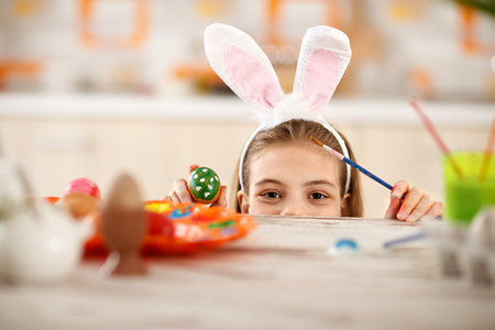 Girl with rabbit ears on head sticking under table and show colorful Easter egg