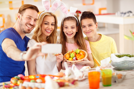 Cheerful family make selfie with basket of colorful Easter eggs