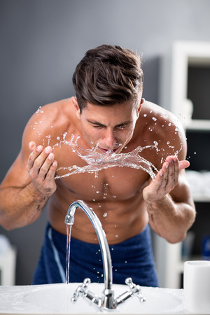 Young man washing face with clean water, morning hygiene