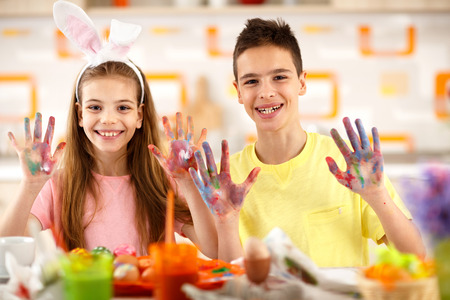 Smiling boy and girl show painting hands with eggs color