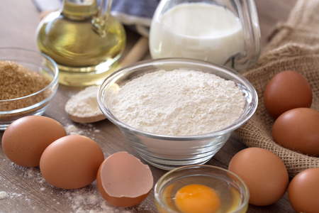 eggs and flour basic ingredients for baking on wooden table background