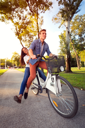 Young excited couple enjoying bicycle ride