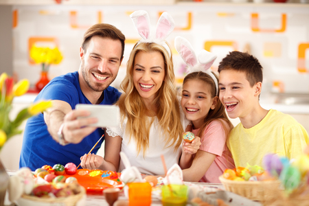 Family selfie in kitchen while painting Easter eggs
