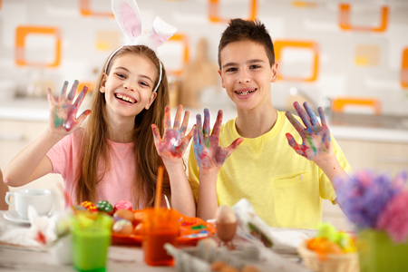 show of hands: Cheerful children show colorful painted hands with paint for eggs