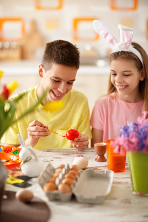 Boy and girl painting red Easter egg in kitchen