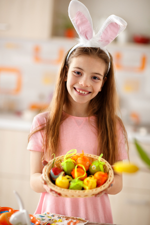 Lovely female child show basket with colorful Easter eggs