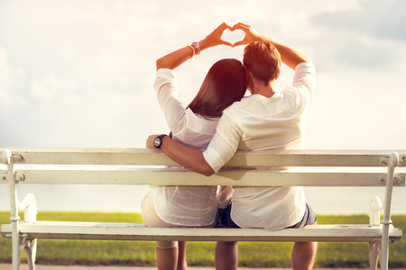 Affectionate couple making a love symbol with hands photo