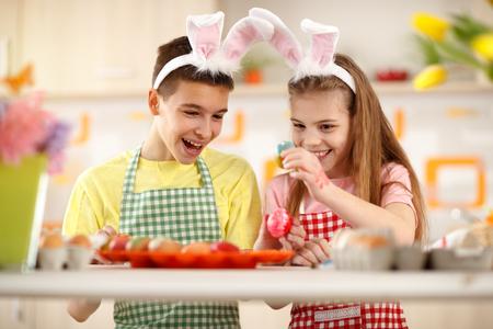 children celebration: Cheerful children coloring eggs for Easter celebration