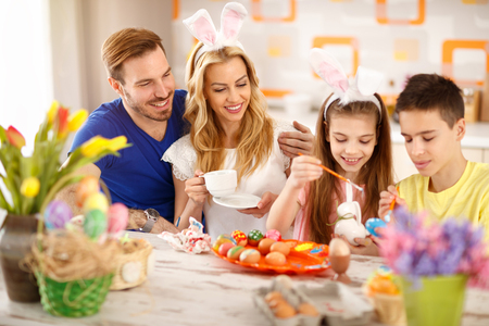 Children painting Easter eggs with parents in kitchen Stock Photo