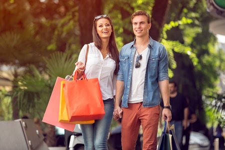 Happy couple with shopping bags walking and laughing photo